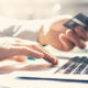 Closeup businessman working with generic design notebook. Online payments, hands keyboard. Blurred background, film effect