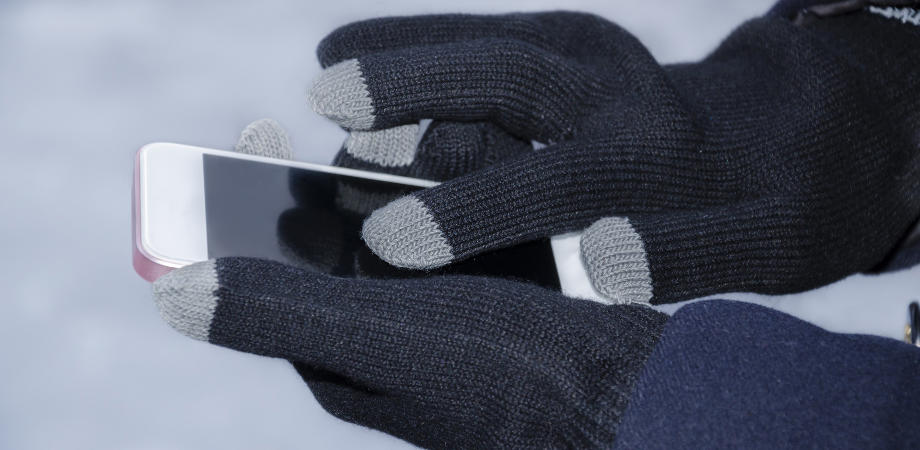 Girl's hands, in special gloves for typing on a gadget in winter, close-up
