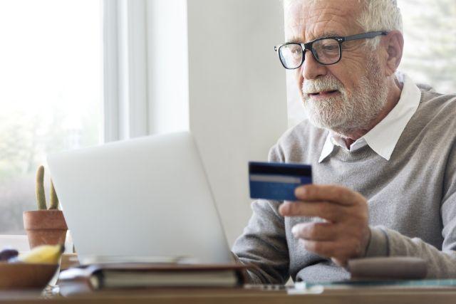 Starszy mężczyzna używający karty płatniczej